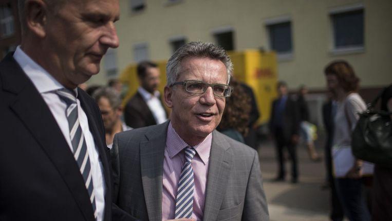 Duits minister van Binnenlandse Zaken Thomas de Maiziere (midden) bij een bezoek aan een asielcentrum nabij de Poolse grens.