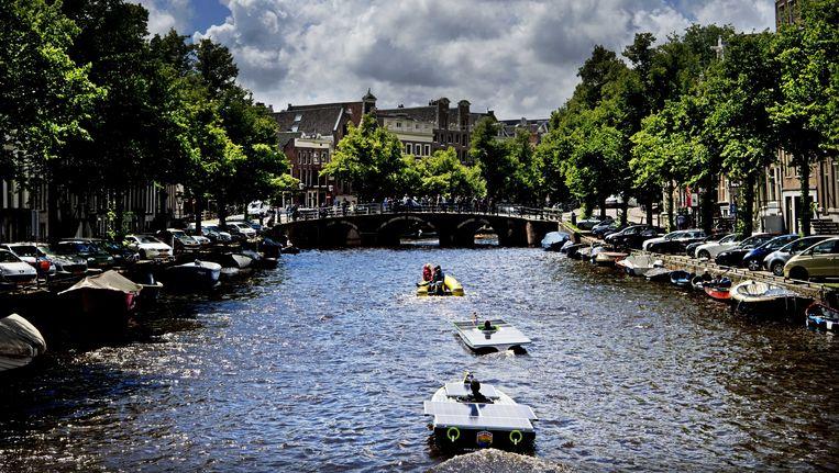 Door zonne-energie aangedreven boten van Dutch Solar Challenge varen door de grachten om aandacht te vragen voor duurzame energie. Beeld anp