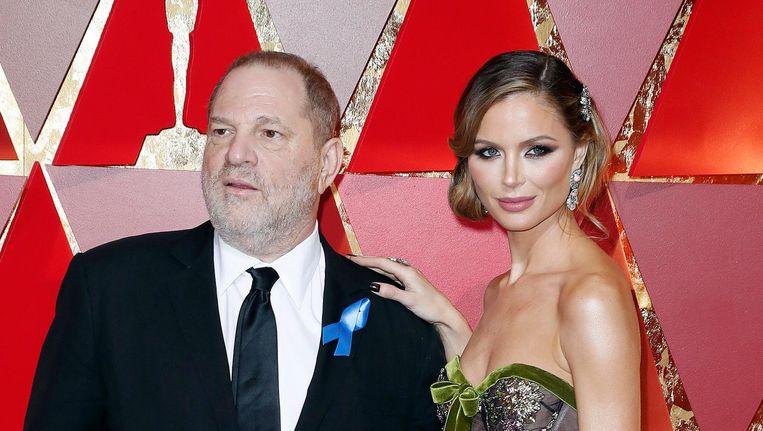 Harvey Weinstein, links, met designer Georgina Chapman, zijn echtgenote die sinds kort van hem wil scheiden, tijdens de feestelijke uitreiking van de Oscars in februari dit jaar. Beeld null
