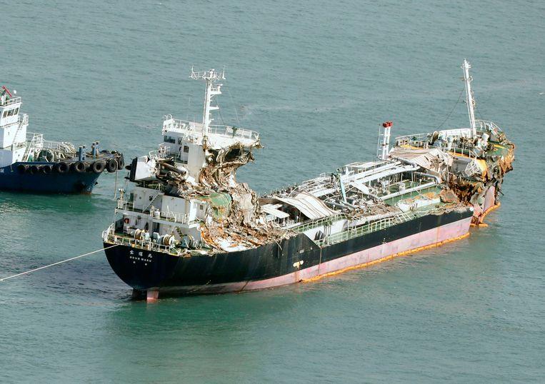 De beschadigde tanker wordt weggesleept bij de brug die de luchthaven van Kansai verbindt met het vasteland. Zo'n drieduizend passagiers kwamen vast te zitten op het vliegveld. In de loop van woensdag plaatselijke tijd werden ze via boten en een busverbinding 'bevrijd' en naar het vasteland gebracht.