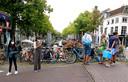 Enkele toeristen met mondkapje op een brug over een van de grachten in het centrum van Delft.