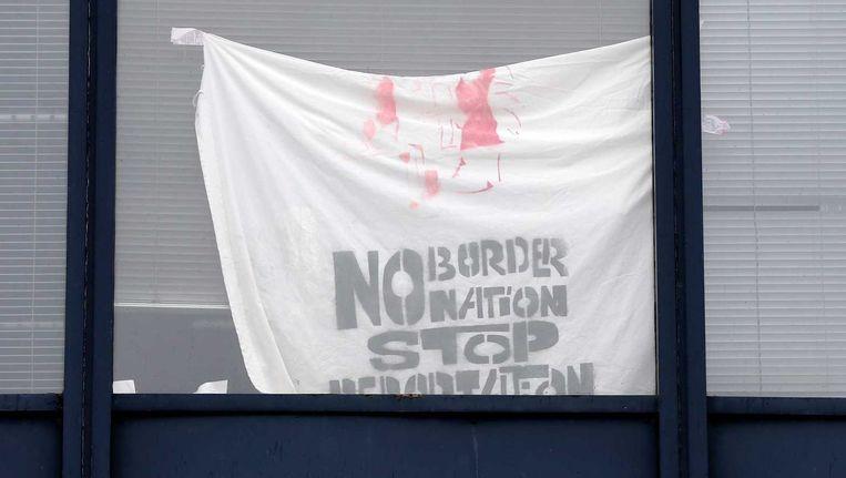 Een spandoek achter een raam van het pand aan de Jan Tooropstraat in Amsterdam waar de asielzoekers nu verblijven. Beeld anp