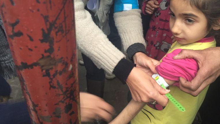 Een medewerker van UNICEF meet de arm van een ondervoed kind in Madaya. Beeld AFP