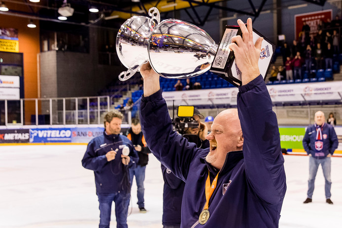 Coach Alexander Jacobs toont trots de imposante cup van de Nederlandse titel.