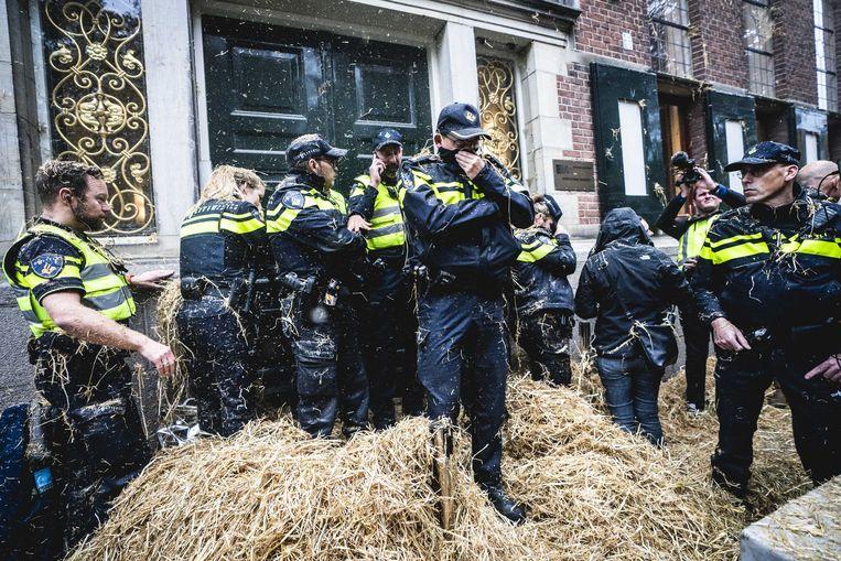 Politieagenten worden maandag belaagd met stro tijdens boerenprotest voor het provinciehuis in Groningen. Belangenbehartiger LTO Noord riep op tot de actie en eist een opschorting van de beleidsregels rond stikstof. Beeld ANP SIESE VEENSTRA