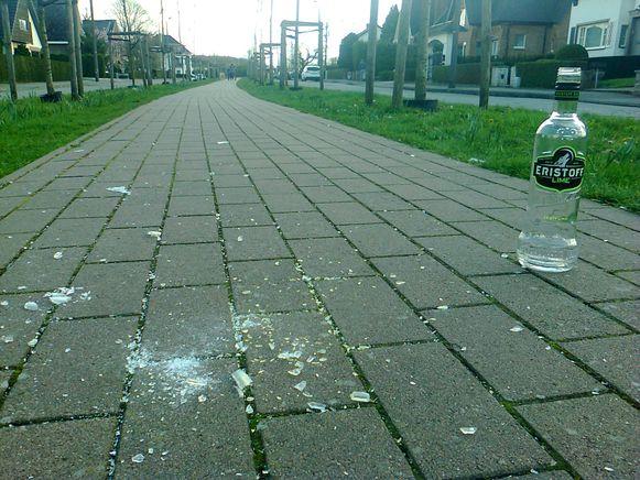 Glasscherven van kapotte flessen en hele flessen lagen overal in de wijk.