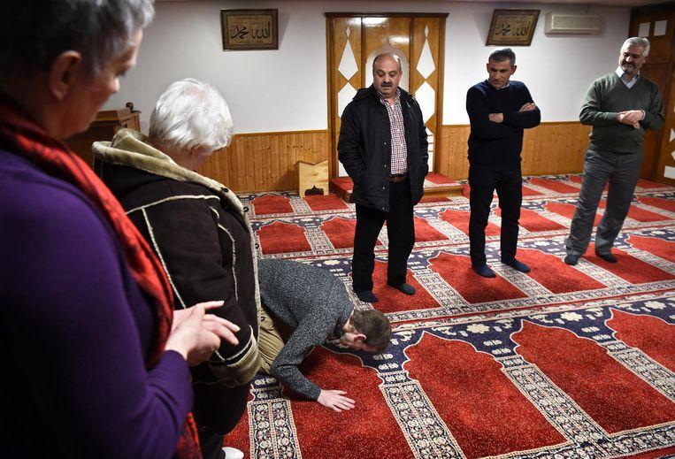 Eén van de gasten doet voor hoe hij denkt dat men bidt in een moskee. Beeld Marcel van den Bergh / de Volkskrant