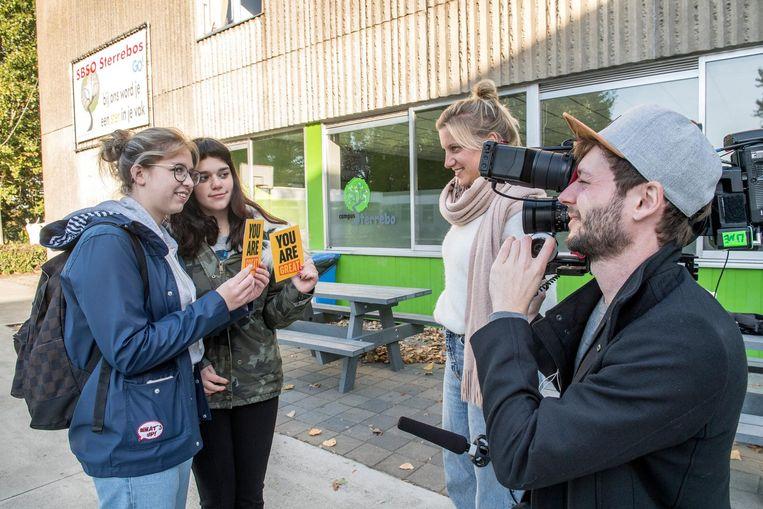 Deze jongedames tonen hun postkaartjes aan de cameraploeg.