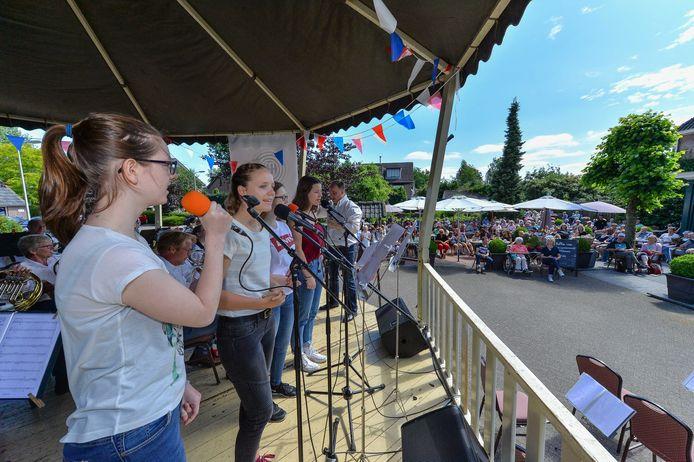 Het orkest krijgt hulp van vier zangeressen. Op de achtergrond een vol terras van café Koerkamp.