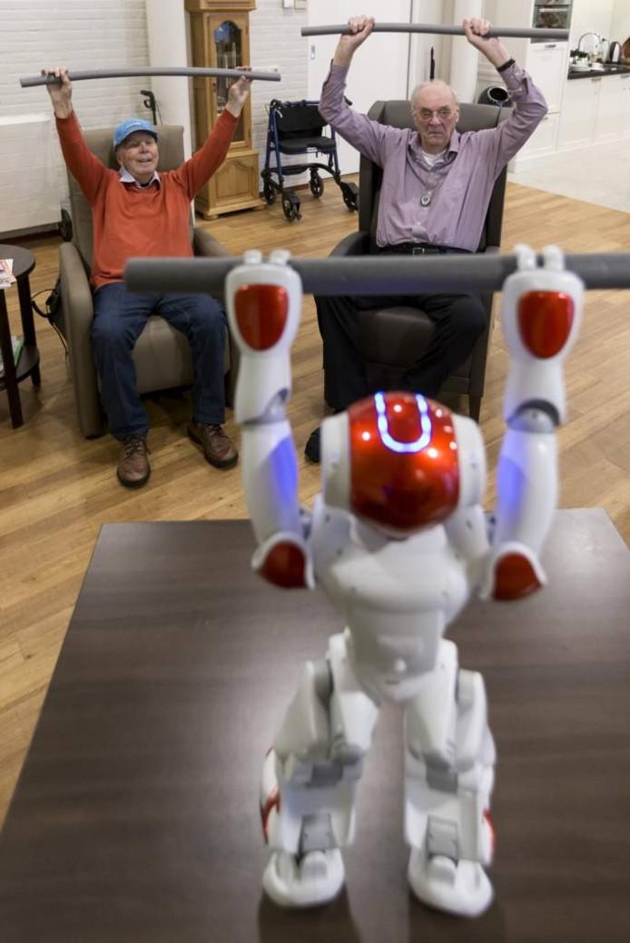 Robot Zora verleidt ouderen om mee te doen met een gymnastiekles. foto Marc Bolsius