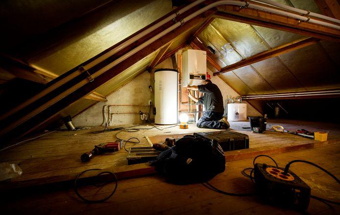 Een installateur is bezig met het installeren van een warmtepomp bij een verwarmingsketel, als onderdeel van een project om een jaren 60-woning energiezuinig te maken.