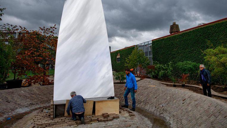Anish Kapoor (rechts) houdt toezicht bij het plaatsen van Sky Mirror (for Hendrik) voor museum De Pont in Tilburg. Beeld Dolph Cantrijn
