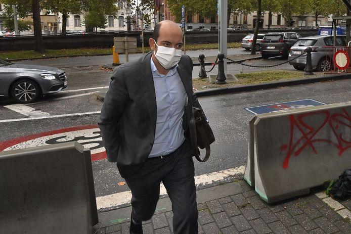 Staatssecretaris Michel bij zijn aankomst aan het hoofdkwartier van MR. Achter hem zijn foutgeparkeerde wagen.