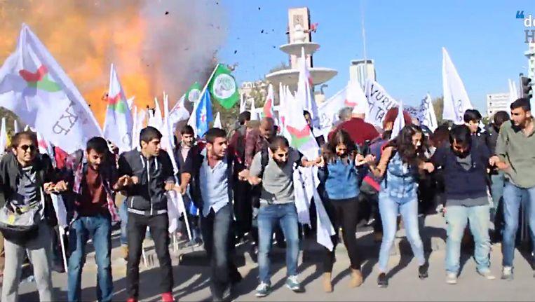Het moment van de bomexplosie op zaterdag. Betogers demonstreren in de buurt van het station in Ankara voor een vreedzame oplossing van het conflict in Zuidoost-Turkije als achter hen een bom afgaat. Beeld EPA