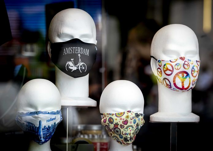 Stoffen, herbruikbare mondkapjes in een etalage in de Damstraat. De gemeente Amsterdam gaat stoffen kapjes verstrekken aan klanten van de Voedselbank.