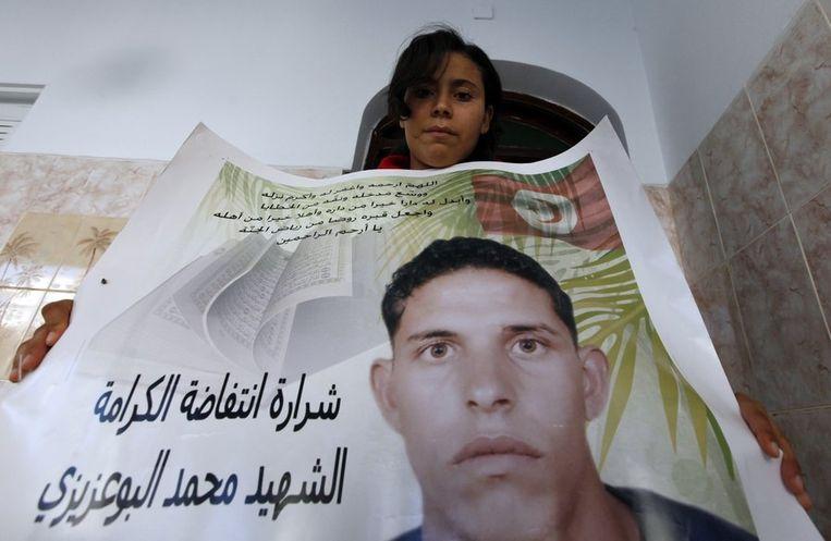 De zus van Mohamed Bouazizi, met z'n afbeelding. Beeld reuters