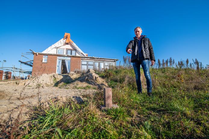 Gerrit van den Brink bij de dubbele woning aan de Oudedijk, waar een bouwstop op rust. Hij wil het huis verplaatsen. De gevel zou dan uitkomen op de plek van de baksteen.