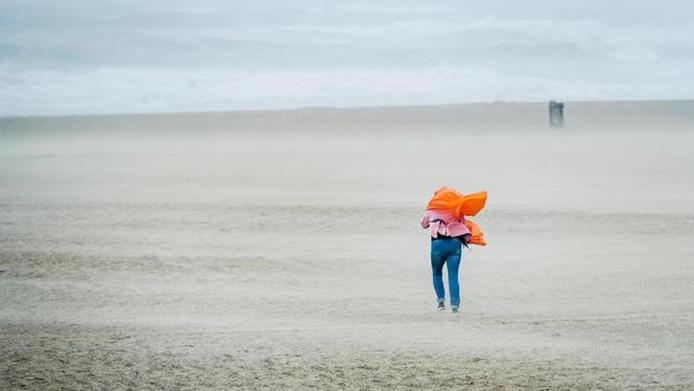 Een wandelaar trotseert de wind op het strand van Scheveningen tijdens de zomerstorm van begin juni.