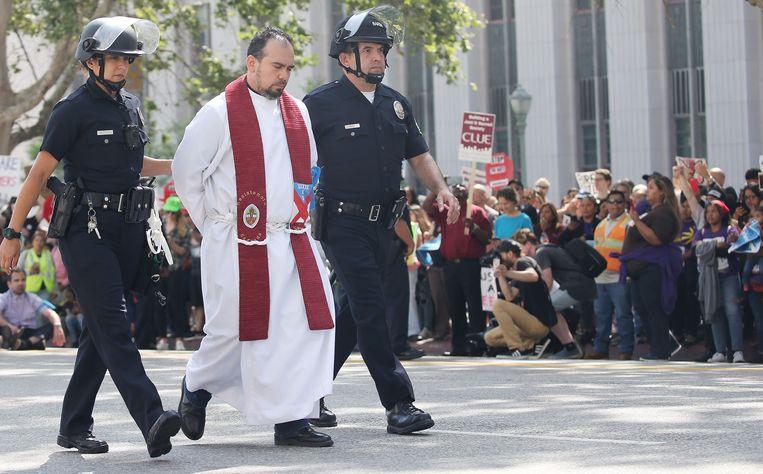 Een priester wordt gearresteerd tijdens een demonstratie tegen het bezoek van de Amerikaanse Justitieminister Jeff Sessions in Los Angeles waarbij de demonstranten een straat afsloten.