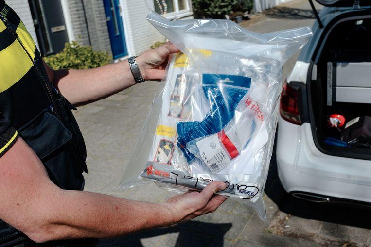 De dienstwagen van wijkagent Van Grinsven ligt vol beschermende materialen, zoals dit pak waarin hij kan reanimeren. 'Maar tegen iemand die ligt te vechten voor z'n leven, kun je niet zeggen: Wacht effe, ik doe eerst een overall aan' Beeld Merlin Daleman