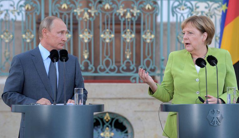 De Russische president Vladimir Poetin en de Duitse kanselier Angela Merkel in gesprek. Beeld null