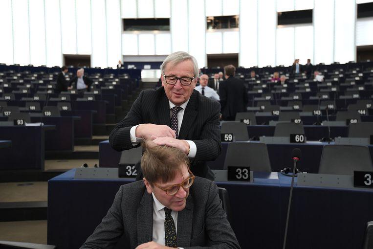 De voorzitter van de Europese Commisssie Jean-Claude Juncker ordent het haar van Europarlementariër Guy Verhofstadt. Juncker dankt zijn baan aan het feit dat zijn fractie bij de Europese parlementsverkiezingen groter werd dan bijvoorbeeld de liberalen van tegenkandidaat Verhofstadt. Beeld AFP