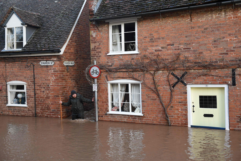 Een man baant zich een weg door het water in de stad Tenbury Wells in het westen van Engeland. Groot-Brittannië heeft veel overlast van storm Dennis.