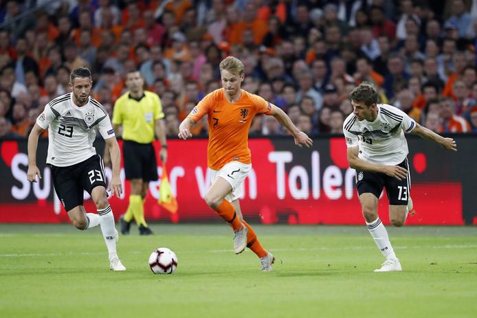 Frenkie de Jong schudt Thomas Müller en Mark Uth van zich af.