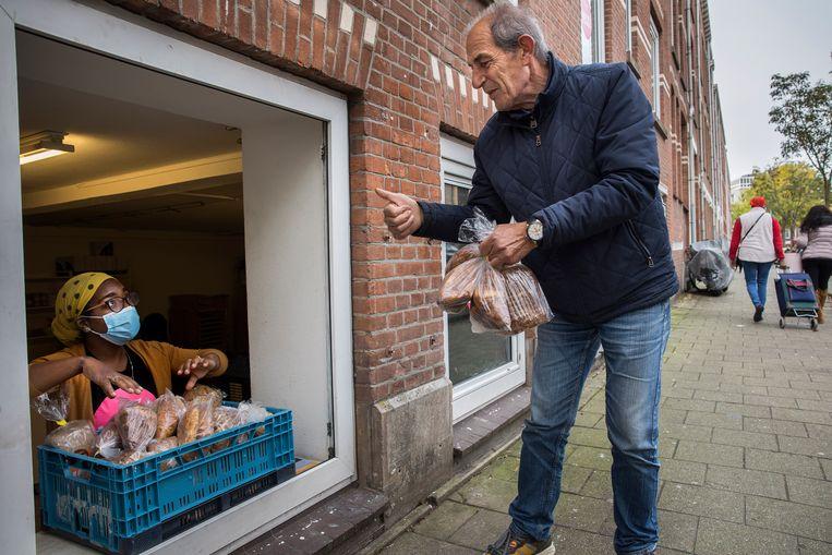 Vrijwilliger Alida Adriaan helpt een klant van de Rotterdamse weggeefwinkel.    Beeld Arie Kievit