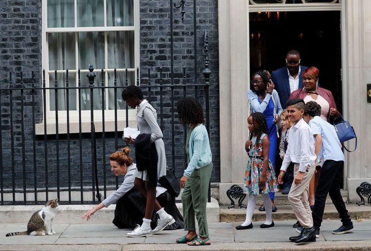 Schoolkinderen aaien Larry the cat, na hun bezoek aan premier Johnson in Downing Street. Beeld AP