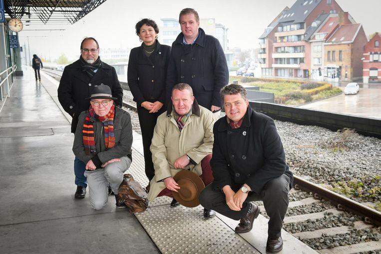 De zes politici in het Roeselaarse station. Vlnr., rechtstaand: Peter Roose (sp.a), Sabien Lahaye-Battheu (Open Vld) en Bert Maertens (N-VA). Vlnr., geknield: Bart Caron (Groen), Stefaan Sintobin (Vlaams Belang) en Roel Deseyn (CD&V).