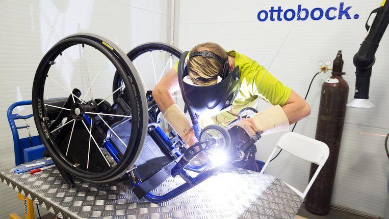 Een medewerker last turbowieltjes onder een rolstoel. Beeld Inge Hondebrink