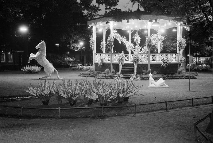Verlichte kiosk en beelden van bloemen in bloemenfeest van Dahliavereniging, Stadspark 1957.