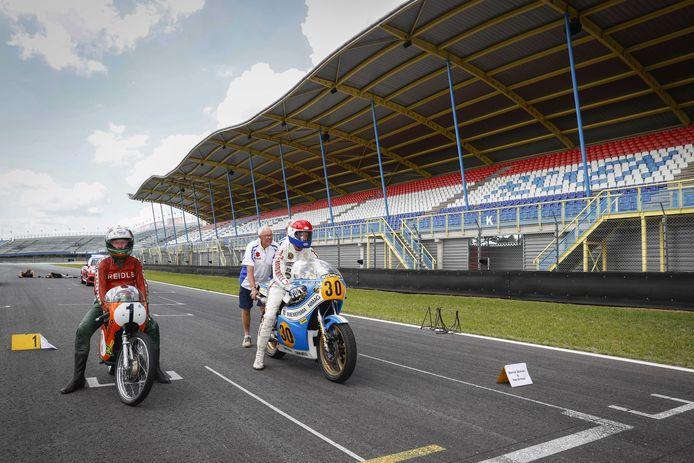 Coureurs Jan de Vries (L) en Wil Hartog gaan van start voor een lege hoofdtribune voor het rijden van een aantal ronden op het circuit tijdens de viering van de 95ste verjaardag van de TT Assen.