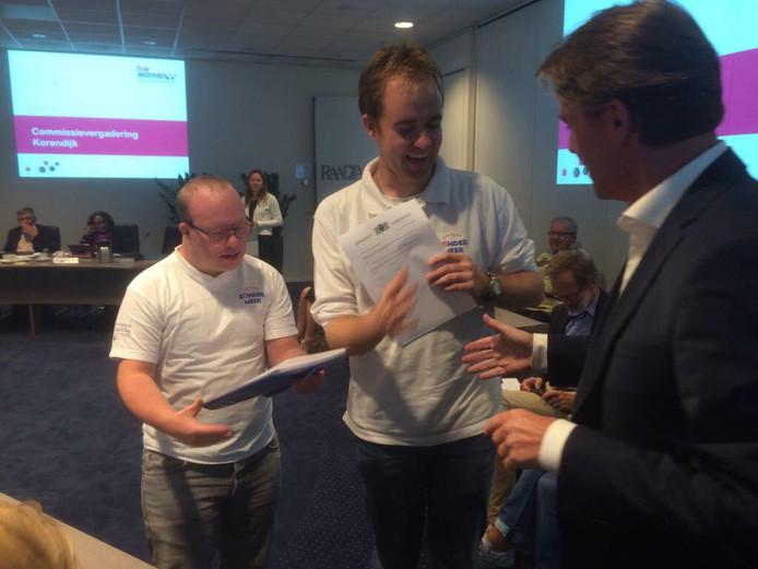 Werknemers van Zonder Meer overhandigen de petitie aan wethouder Paul Boogaard van Korendijk.