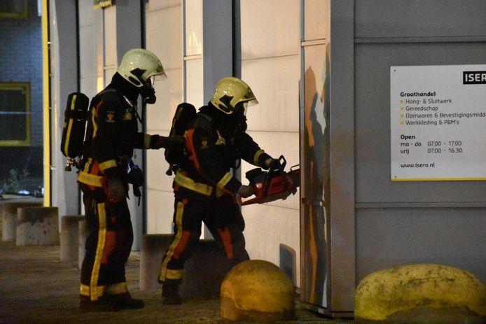 De Brandweer probeert binnen de komen bij de IJzerwarenhandel aan de Marconistraat in Gouda waar brand woedt.