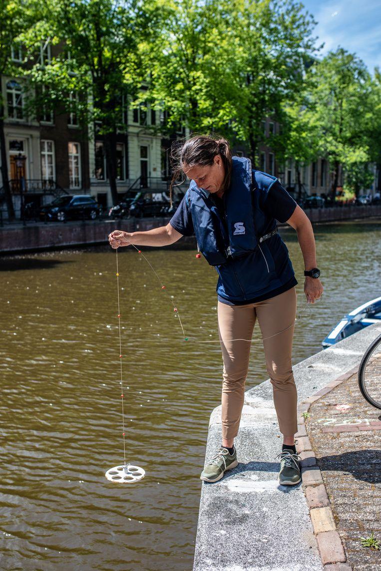 Kirsten Vendrig van Waternet meet met met een speciaal instrument de helderheid van het Amsterdamse grachtenwater. Beeld Nosh Neneh