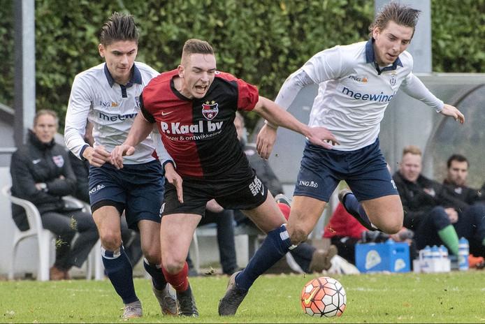 Coen Maertzdorf, vleugelaanvaller van De Treffers, in de tang bij twee spelers van Koninklijke HFC.
