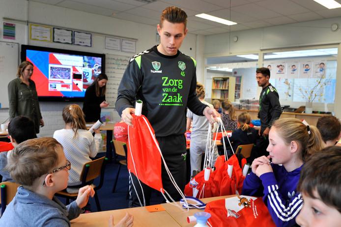 Voetballers Andreas Ludwig van FC Utrecht en rechts  Bram van Eijk van Jong FC Utrecht delen promotie materiaal uit aan de leerlingen van Basisschool De Wegwijzer.