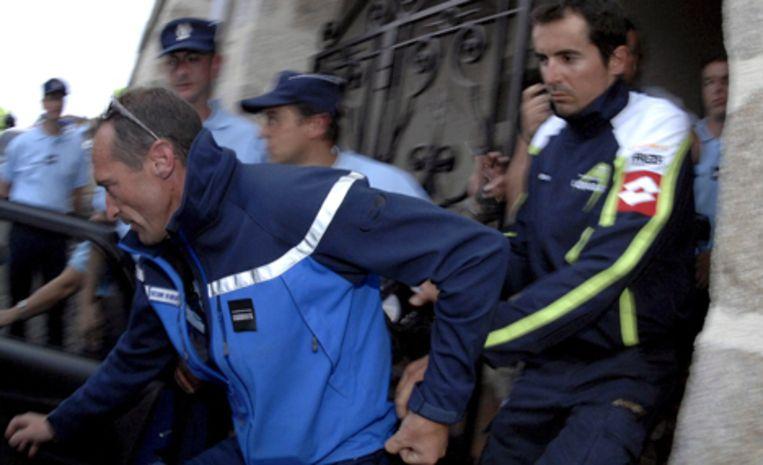 Franse agenten voeren de Spaanse wielrenner Manuel Beltran geboeid af, na een inval in het hotel in Le Rouget, waar de ploeg van Beltran gisteren was ondergebracht. Foto EPA//Nicolas Bouvy Beeld