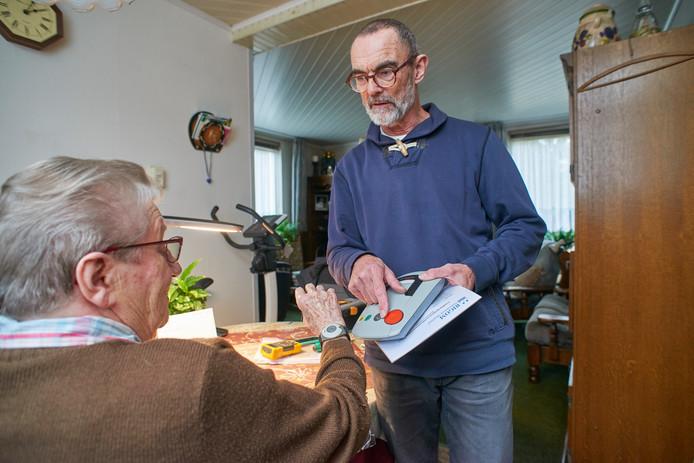 Ignace van Dommelen geeft uitleg over het alarmsysteem bij een cliënt thuis