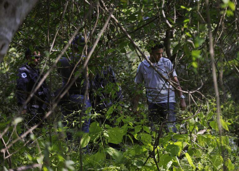 Agenten bij een massagraf met verbrande lichamen. Beeld reuters
