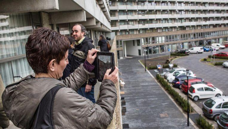 Een jurylid van de Mies van der Rohe Award neemt een foto van de flat Kleiburg in Amsterdam-Zuidoost. Beeld Floris Lok