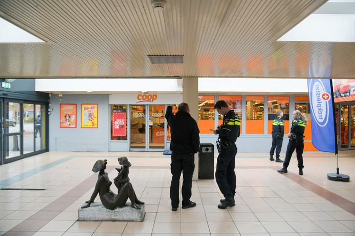De politie doet buurtonderzoek na een gewapende overval op de Coop in winkelcentrum Notenhout.