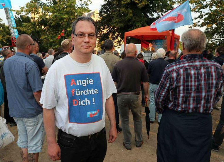 Een AfD aanhanger afgelopen donderdag in Schwerin met de tekst 'Angie wees bang' op zijn T-shirt. Beeld epa