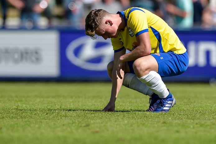 OSS'20-speler Joep Engelen staart in het gras. De promotie van de club uit Oss naar het hoogste amateurvoetbalniveau gaat niet door.