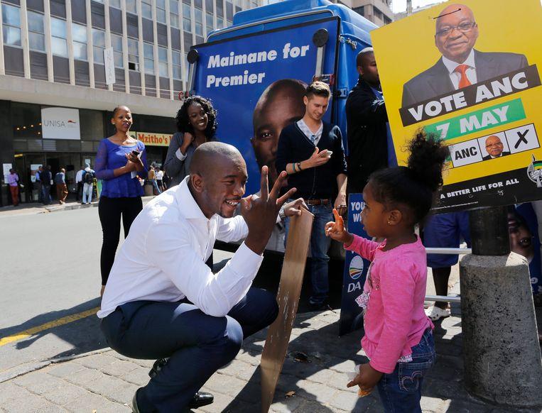 (22 april 2014)  Mmusi Maimane praat met een jong meisje tijdens de lancering van de laatste fase lanceert van de affiches van de DA voor de algemene verkiezingen in Zuid-Afrika.  Beeld EPA / Kim Ludbrook