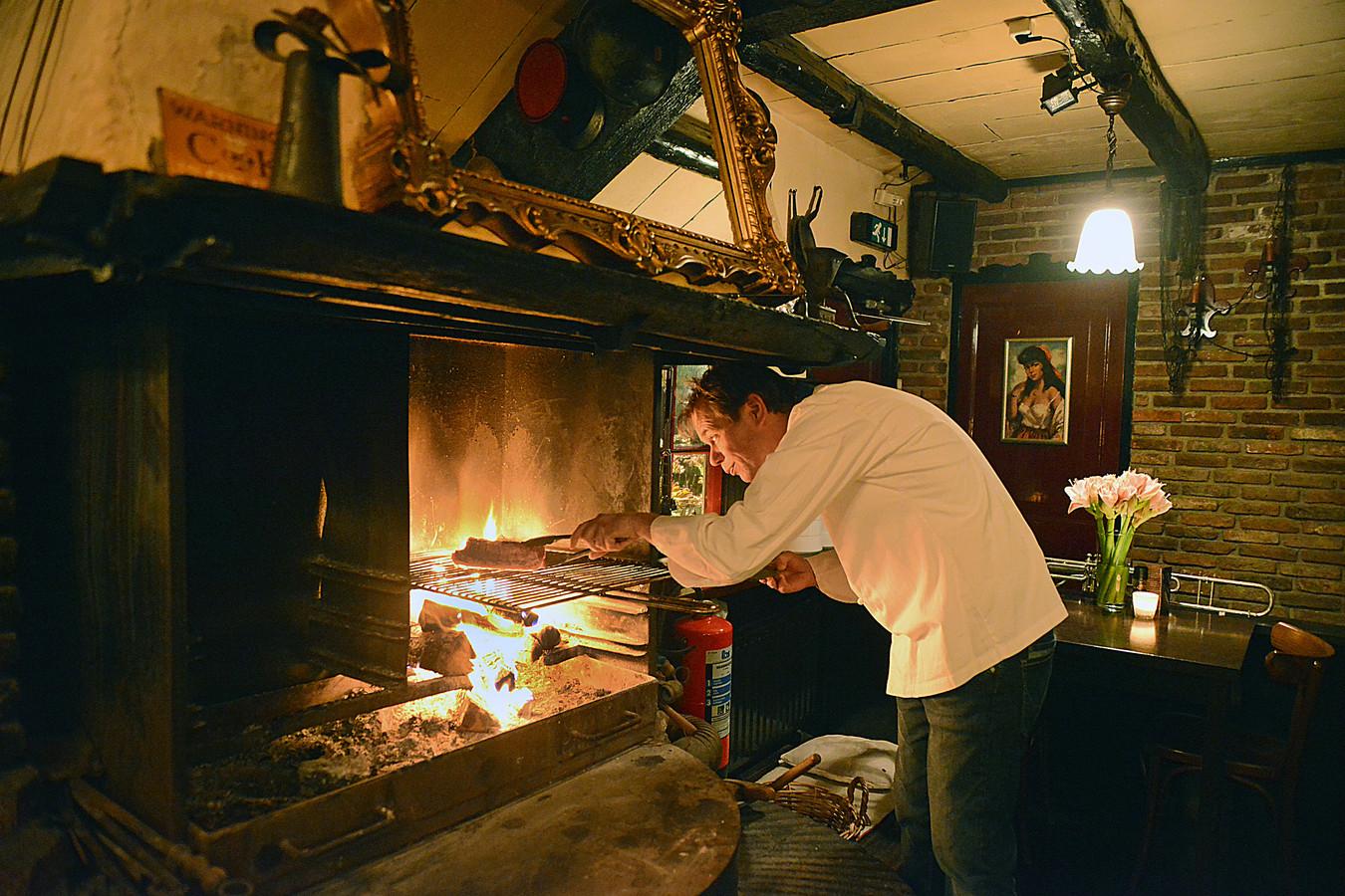 Evert van Dilst maakt het vlees klaar boven het smidsevuur middenin de zaak.