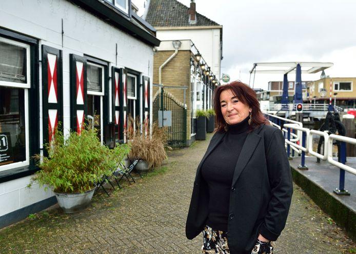 Flory de Ruiter voor haar woning. Op de achtergrond het pand waar het in de nacht van 1 op 2 januari helemaal misging.