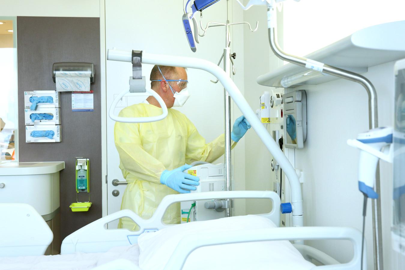 Artsen dragen beschermende overkleding, rubberen handschoenen, een mondkapje en een bril als ze een patiënt in de isolatiekamer behandelen.